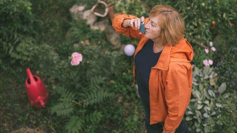 Eine Frau mit Asthma benutzt ein Inhalier-Gerät.