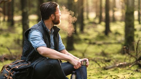Ein Mann sitzt in einem Wald auf einem Koffer und hält den Becher einer Thermoskanne in einer Hand. Er blickt in die Ferne, zwischen Bäumen hindurch - vor seinem Gesicht verdunstet eine Atemwolke.