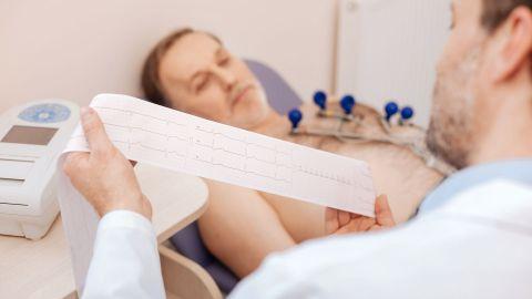 AV-Block: Ein Arzt begutachtet die Ergebnisse eines EKG, ein Patient liegt auf einer Behandlungsliege.