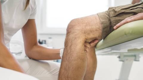Eine Frau in weißer Arbeitskleidung hält das Knie einer männlichen Person, die auf einem Behandlungsstuhl sitzt.