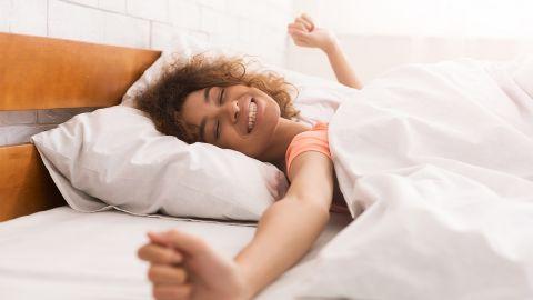 Biorythmus: Eine Frau liegt im Bett und räkelt sich. Sie wirkt ausgeschlafen und zufrieden. Das Zimmer ist Sonnendurchflutet.