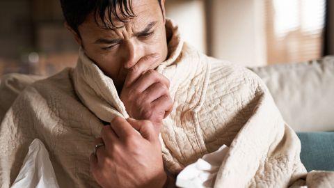 Entzündung der Atemwege: Ein Mann sitzt auf einer Couch, hat seinen kompletten Oberkörper in eine wärmende Decke gehüllt und greift sich mit einer Hand an die Nase. Sie scheint verschnupft zu sein.
