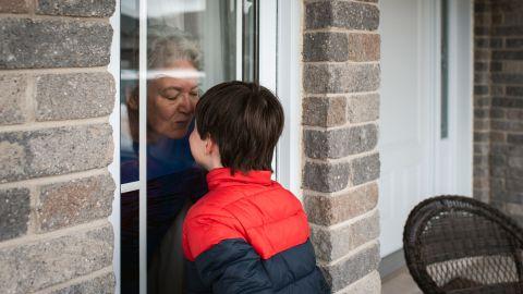 Eine ältere Frau und ein Junge stehen sich nah gegenüber - getrennt durch ein Fenster. Die Frau befindet sich in der Wohnung, der Junge draußen. Beide nähern ihre Gesichter der Fensterscheibe, die Frau deutet einen Kuss an..