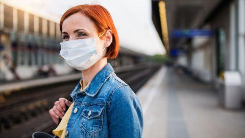 Eine Frau steht an einem verlassenen Bahnsteig und trägt eine Mund-Nasen-Schutzmaske. Mit einer Hand hält sie eine Tasche fest, die an ihrer Schulter liegt. Die Frau schaut in Richtung Bahngleise.