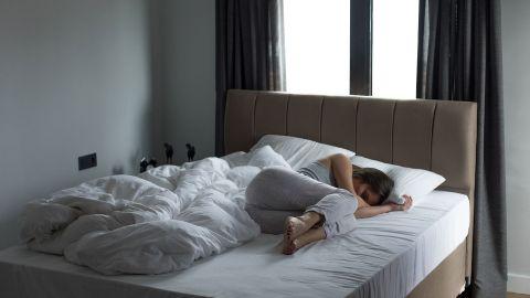Depression: Eine Frau liegt zusammengekauert in einem großen Bett.
