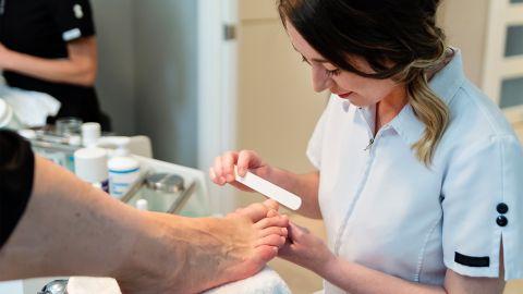 Diabetischer Fuß: Eine junge Dame führt eine Fußpflege durch. Sie feilt die Fußnägel der Person, die gerade behandelt wird.