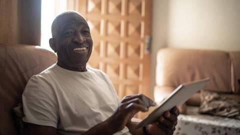Lächelnder Mann im Sessel, der gerade ein Tablet bedient.