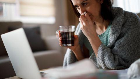 Eine Frau schaut auf den Bildschirm eines Laptops, der vor ihr auf einem Tisch steht. Mit einer Hand hält die Frau einen Becher Tee, mit der anderen Hand ein Taschentuch unter ihre Nase. Die Frau ist offenbar erkältet.