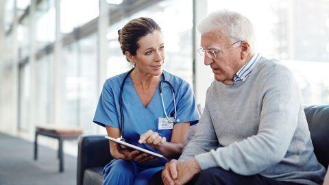 Digitalisierung im Gesundheitswesen: Eine Ärztin und ein Mann sitzen auf einer Couch vor einer großen Fensterfront. Die Ärztin schaut den Mann an und zeigt mit einer Hand auf ein Tablet, das sie in der anderen Hand hält. Der Mann schaut auf das Tablet.