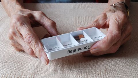 """Elektronischer Medikationsplan (eMP): Eine ältere Frau hält eine Tablettenbox aus Kunststoff in den Händen. Auf der Box steht """"Donnerstag"""". In einem der Fächer liegen eine ovale Tablette und eine Kapsel."""