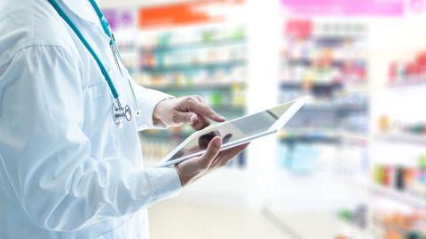 E-Rezept: Ein Mann im weißen Kittel steht in einer Apotheke. In der rechten Hand hält er ein Tablet. Mit dem Zeigefinger der linken Hand deutet der Mann auf den Bildschirm. Im Hintergrund zwei Schränke, in denen Medikamente stehen.