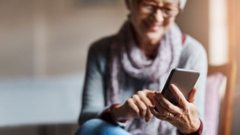 Eine ältere Frau mit Brille sitzt auf einer Couch. Die Frau hält ein Smartphone in der linken Hand, tippt mit der rechten Hand auf den Bildschirm und lächelt.