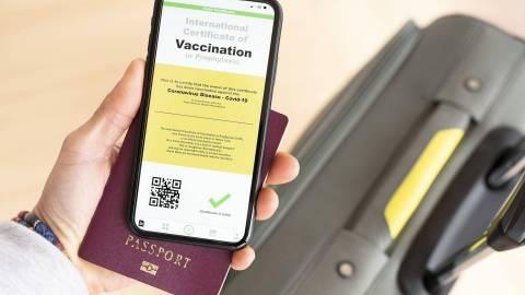Eine Hand hält ein Smartphone und einen Reisepass. Auf dem Bildschirm des Smartphones wird ein digitaler Impfnachweis angezeigt. Im Hintergrund ist ein Reisekoffer zu sehen.