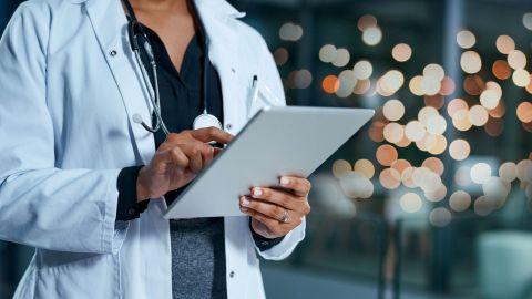 Digitale Medizin: Eine Ärztin hält ein Tablet in der Hand und tippt mit der anderen Hand auf den Bildschirm.