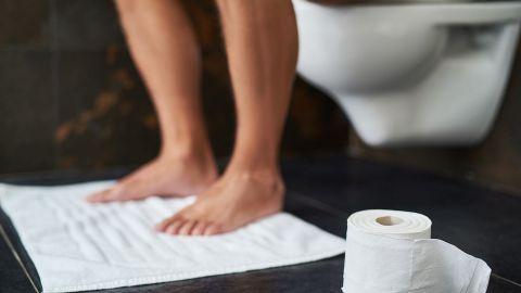 Ein Mann sitzt auf einer Toilette, womöglich hat er Durchfall.