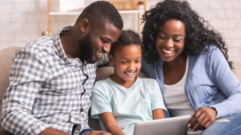 E-Kinderuntersuchungsheft: Mutter, Vater und ein junges Mädchen sitzen gemeinsam auf dem Sofa. Das Mädchen sitzt zwischen den Eltern und hält ein Tablet in der Hand. Alle drei schauen auf den Bildschirm des Geräts.