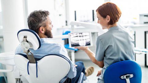 E-Zahnbonusheft: Ein Patient sitzt auf dem Behandlungstuhl beim Zahnarzt. Die Ärztin sitzt neben ihm und zeigt ihm die Röntgenaufnahme seines Gebisses auf einem Tablet.