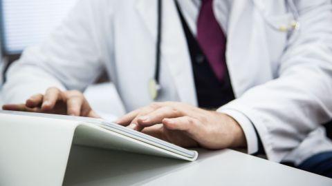 Ein Arzt sitzt am Schreibtisch und tippt etwas auf der Tastatur eines Tablets.