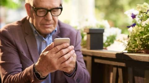 Ein älterer Herr mit Brille sitzt im Außenbereich eines Cafés und schaut auf den Bildschirm seines Smartphones.