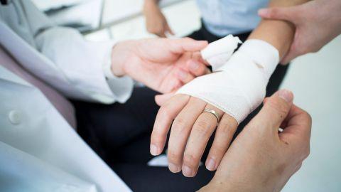 Erysipel: Ein Mann erhält einen Verband ums Handgelenk.