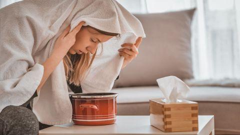Eine erkältete Frau inhaliert Wasser, um ihre Atemwege zu befreien. Neben ihr auf dem Tisch liegt eine Box mit Taschentücher.