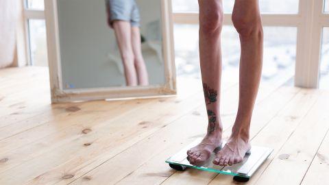 Essstörung: Eine untergewichtige Frau steht mit dem Rücken zu einem Ganzkörperspiegel auf einer Waage.