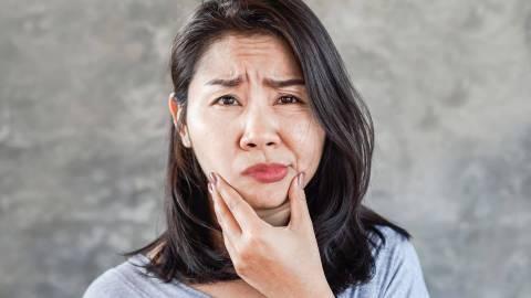 Eine Frau fasst sich an die Kinnregion und schaut ernst in die Kamera. Ihre rechte Gesichtshälfte ist langgezogen, die Mundpartie ist schief.