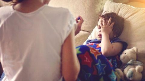 Fieber? Ein Kind, das erschöpft aussieht, liegt auf einer Couch und fasst sich an den Kopf.