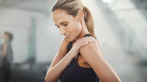 Eine Frau in Sportkleidung und leicht schmerzverzerrtem Blick greift sich an die Schulter.