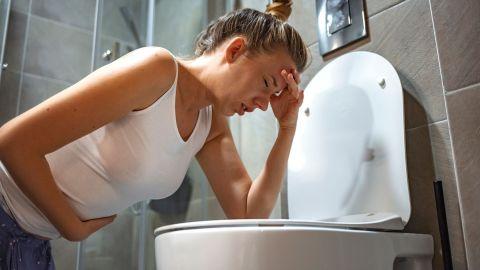 Gastritis: Eine Frau stützt sich mit einem Ellbogen auf einer Klobrille ab, hält sich den Bauch und fasst sich an den Kopf. Der Frau scheint es nicht gut zu gehen.