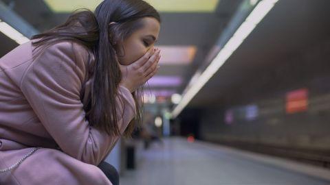 Generalisierte Angststörung: Eine Frau hat die Augen geschlossen, sitzt nach vorne gebeugt und legt ihren Kopf in beide Hände.