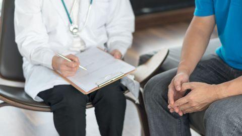 Ein Urologe hält einen Fragebogen und einen Stift in der Hand, neben ihm sitzt ein Mann.
