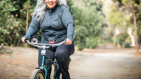 Eine ältere Frau fährt mit einem Fahrrad einen Waldweg entlang. Sie lächelt.