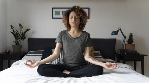 Gesund mit Entspannung: Eine Frau sitzt auf ihrem Bett im Schneidersitz und meditiert. Sie hat beide Hände auf ihren Knien abgelegt und die Hände in Chinmudra-Haltung. Sie hat die Augen geschlossen und atmet aus.