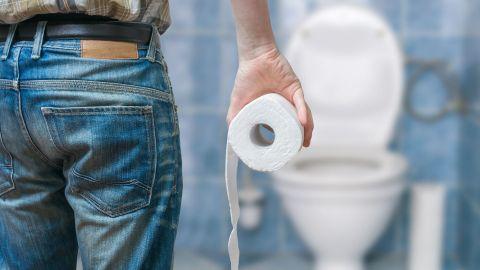 Hämorrhoiden: Ein Mann steht in einem Bad, blickt auf eine Toilette mit geöffneter Klobrille und hält eine Klopapierrolle in der rechten Hand.