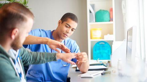 Handgelenksverletzung: Ein Arzt untersucht die Hand eines jungen Mannes.