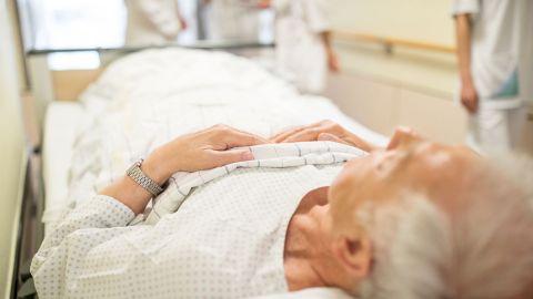 Harnblasenkrebs: Ein älterer Mann liegt mit dem Rücken auf einem Behandlungsbett, das durch den Gang eines Krankenhauses geschoben wird. Um den Mann herum stehen vier Menschen, die weiße Kittel tragen.