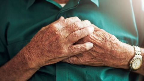 Herzinfarkt: Eine ältere Frau fasst sich mit beiden Händen an den Brustkorb.