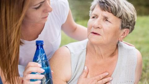 Eine ältere Frau im Sommershirt hat die Hand auf die Brust gelegt. Sie wirkt angestrengt und dreht sich zu einer jüngeren Frau um, die eine Flasche Wasser in der Hand hält.