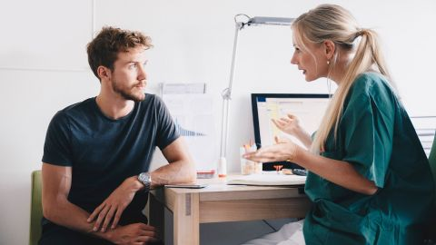 Hodenkrebs: Ein Mann sitzt in einem Behandlungszimmer. Sein Blick ist auf eine Ärztin gerichtet, die ihm gegenüber sitzt und mit ihm spricht.