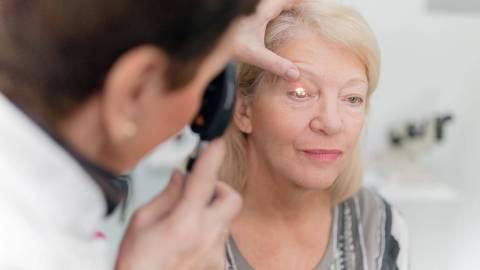 Eine ältere Frau wird untersucht, indem eine Ärztin ihr Augenlid hält und mit einem Messinstrument ins Auge leuchtet.