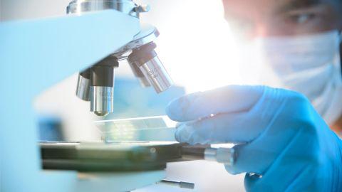 Ein Wissenschaftler, der einen Mundschutz trägt, hält ein streifenähnliches Testobjekt unter ein Mikroskop.