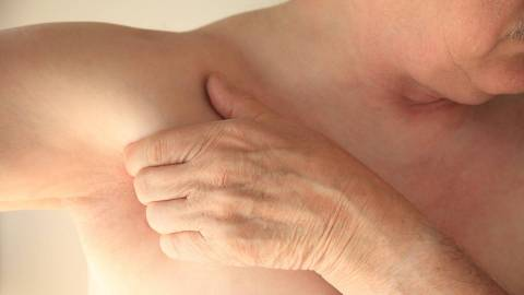 Ein Mann mit freiem Oberkörper streckt seinen rechten Arm zur rechten Seite aus. Mit der linken Hand umgreift er seine Achselhöhle.