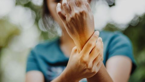 Karpaltunnelsyndrom: Eine Frau hält ihre Arme in die Luft und fasst sich ans linke Handgelenk.