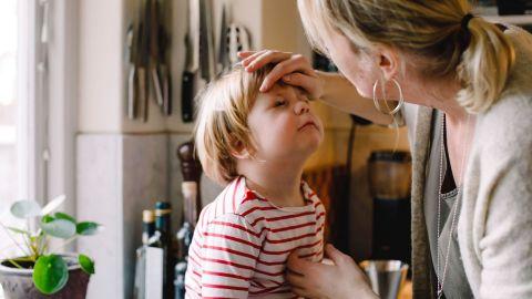 Hornhautnarben und Hornhauttrübungen: Eine Frau steht vor einem kleinen Jungen und berührt ihn mit einer Hand an der Stirn. Dabei schaut sie dem Jungen in ein Auge.