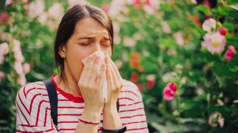 Eine Frau im T-Shirt schnäuzt sich in ihr Taschentuch. Im Hintergrund sind blühende Blumen zu sehen.