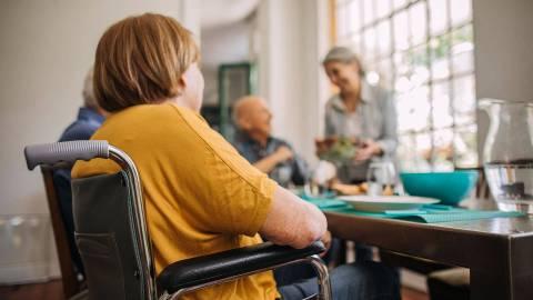 Eine Person im Rollstuhl sitzt mit anderen Menschen an einem gedeckten Tisch. Im Hintergrund serviert eine Frau Essen in einer Schüssel. Im Vordergrund sitzt eine Dame im Rollstuhl.