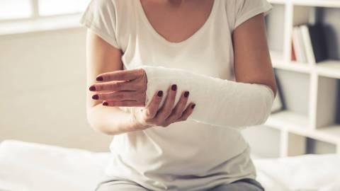 Nahaufnahme einer Frau mit geschientem Unterarm, die auf einer Behandlungsliege sitzt.