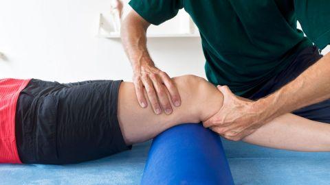 Ein Physiotherapeut presst eine Hand an das Schienbein eines Mannes, der auf einer Behandlungsliege liegt. Die andere Hand presst der Therapeut an den Bereich unterhalb des Kniegelenks, in welchem die Kreuzbänder verlaufen.