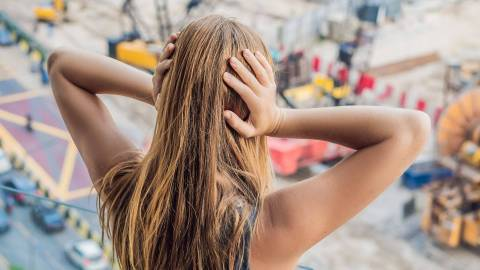 Von hinten ist eine junge weibliche Person zu sehen, die sich die Ohren zuhält. Vor ihr verschwommen eine städtische Umgebung mit Baustellen und Autoverkehr.